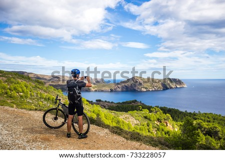 a young guy on a mountain bike trails in Spain and takes a photo on a white phone in the background of the  sea of the rocky coast of the Costa Brava. In a blue helmet and a black backpack.  #733228057