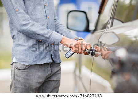 A young guy opens the door to a used car. Used car theme.