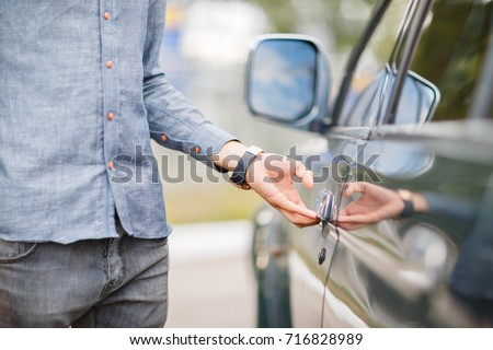 A young guy opens the door to a used car. Used car theme. #716828989