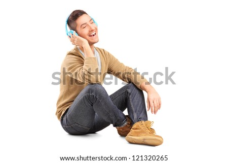 A young guy sitting on a floor and listening music on headphones isolated on white background