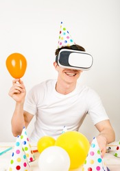 a young guy wearing 3D-reality glasses with a smile on his face and a festive headdress sits at a table surrounded by party details and holds a helium-inflated ball in his hand.
