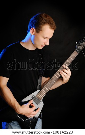 A young guy with an electric guitar on a black background