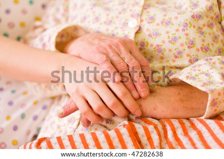 A young hand holding an elderly one. It can be a hand of a carer or a family member.