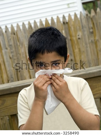 A young handsome boy with a tissue to his nose nurses a cold