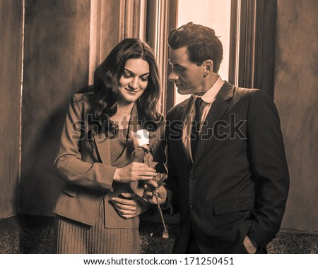 A young handsome businessman is giving a white flower to a pretty businesswoman after work. / Love Between Businessman and Businesswoman