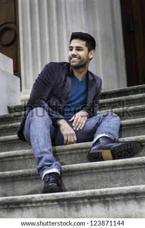 A young handsome guy is sitting on stairs, looking around and smiling./Big smile