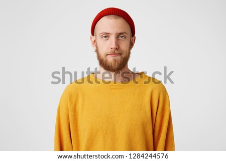 A young handsome guy with a beard,blue eyes, is standing with an indifferent, dissatisfied,apathetic face, not interested,adhering to the conditions, agrees to the conditions, is waiting for his turn