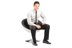 A young handsome malesitting on  chairand posing isolated on white background