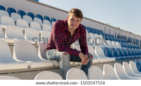 A young handsome man in plaid shirt and jeans sits on a stadium bleachers alone, smiles and looks away in summer.