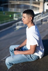 A young handsome man in t-shirt and jeans sits on a stadium bleachers alone