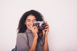 A young happy afro american woman photographer holding retro fil