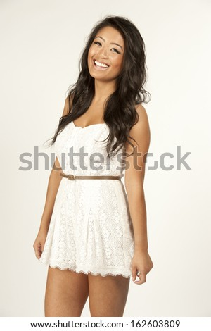 A young happy asian model in a white dress on a white background.