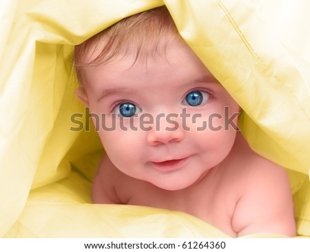 A young happy baby is looking into the camera and has bright blue eyes. The child is on a yellow blanket. Use it for a childhood, parenting or innocence theme.
