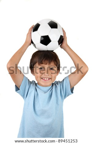 A young happy boy balances a soccer ball on his head - on a white background
