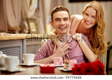 A young happy couple looking at camera in cafe