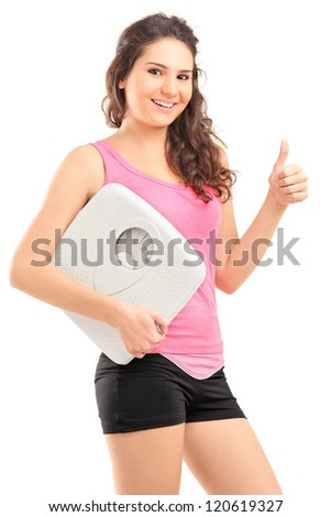 A young happy female holding a weight scale and giving a thumb up isolated on white background
