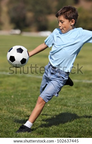 A young happy school age boy prepares to kick a soccer ball in a field on a sunny day