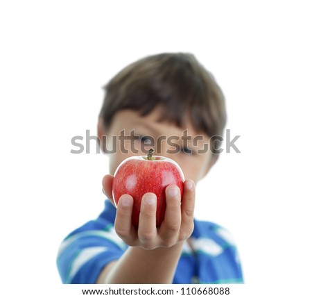A young happy school boy hold an apple out for us on white background