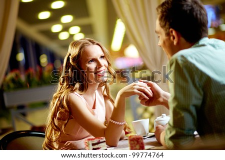 A young happy woman and her boyfriend sitting in restaurant
