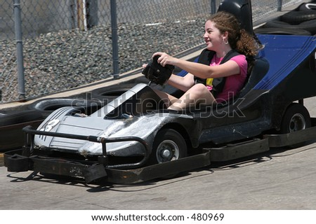 A young having fun racing a go cart around a track