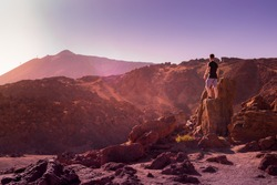 A young hiker wearing a black t-shirt and purple shorts looking at the Teide volcano mounted on a stone surronded by a red, volcanic landscape. Teide National Park, Tenerife, Canary Islands, Spain.