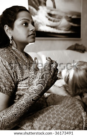 A young Hindu bride receives traditional Henna designs on her arms and hands