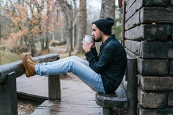 A young hipster sitting on the terrace bench with his legs leaning against a wooden pole and drinking coffee melancholic autumn mood
