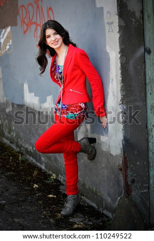 A young hispanic teen woman leans against a wall, smiling, in an urban setting.