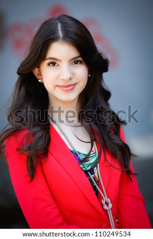 A young hispanic teen woman smiles at the camera in an outdoor setting.