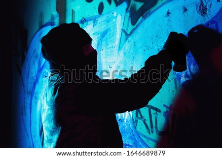 A young hooligan with a spray can stands against a concrete wall with graffiti paintings. Illegal vandalism concept. Street art Foto stock ©