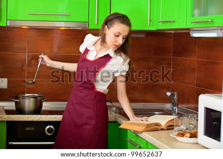 A young housewife is preparing soup with book - stock photo