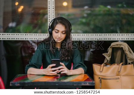 A young Indian Asian woman enjoys music she is streaming to her smartphone via her headphones. She is seated outdoors in a cafe or coworking space during the day and is beautiful and attractive.