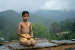 A young indian boy in yellow dhoti meditating in the mountains, with fog.