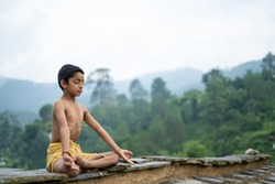 A young indian cute kid doing yoga in the mountains,wearing a dhoti
