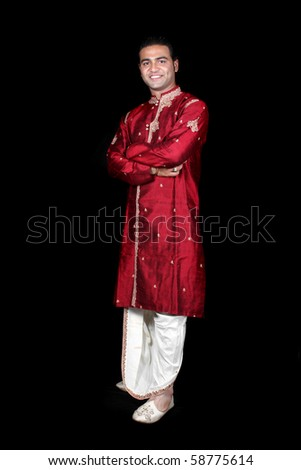 young Indian man in a traditional attire, on black studio background ...