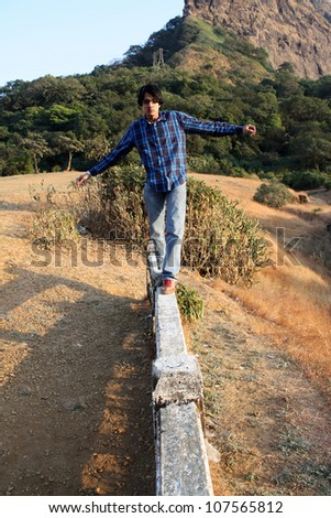 A young Indian man trying to balance himself while walking on a cement beam.