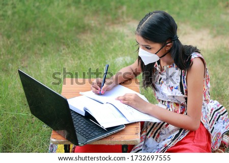 A young Indian rural girl wearing mask is studying online.Study in lock down. Online school classes. Schools closed due to Covid-19. Role of technology during nationwide lock down.Learning at home.