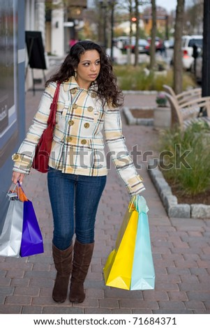 A young Indian woman carrying colorful bags out shopping in the city.
