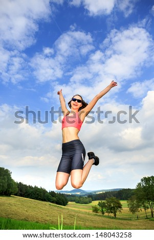 a young jumping woman in front of rural landscape