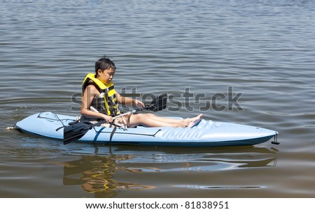 A young Korean boy in a Kayak on a lake
