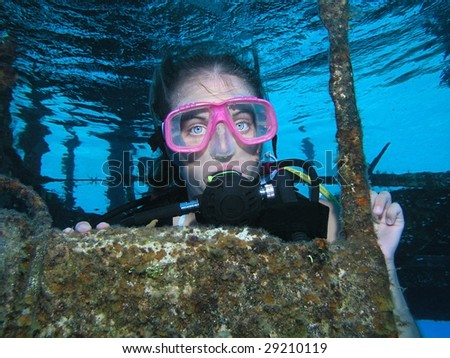 A young lady diver deep underwater on a shipwreck dive site
