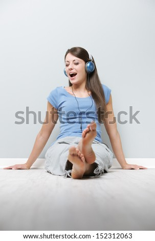 A young lady enjoying music through her headphones