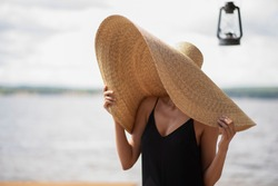 A young lady in a huge straw hat is standing on a bank of the river with beautiful lighting by the sea