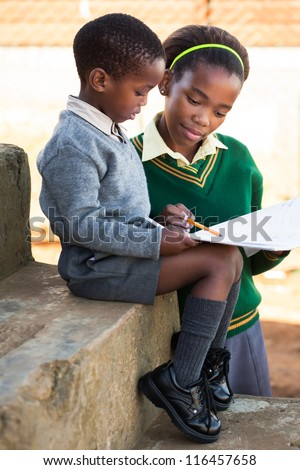 A young lady is helping her little brother with work. - stock photo