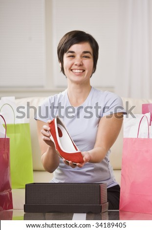 A young lady is holding up a shoe from a box and smiling at the camera.  She is surrounded by shopping bags.  Vertically framed shot.