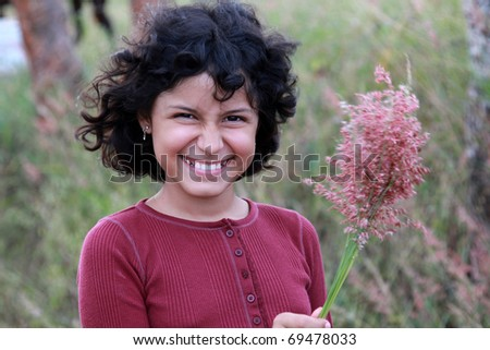 A young Latina girl holding wildflowers in the breeze