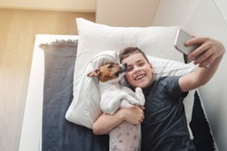 A young laughing boy lies on a bed next to a cute Jack Russell Terrier dog and takes a selfie.