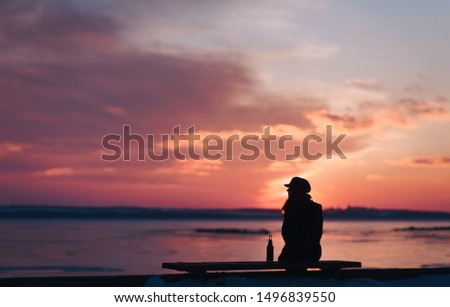 A young lonely girl sits on a bench and is sad next to a bottle of beer. Female alcoholism. Depression and loneliness. Alcohol and concept. Beautiful photo at sunset.