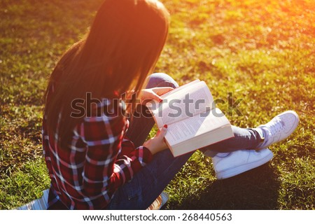 A young lovely woman relax reading an absorbing novel in beautiful the park