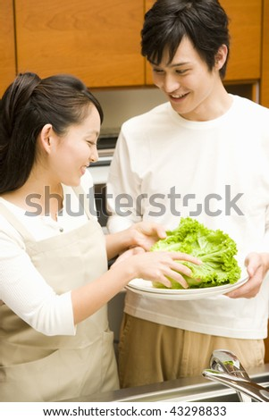 A young loving couple in their kitchen - stock photo